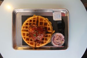 Chicken and waffles with coleslaw and plastic utensils on silver platter.