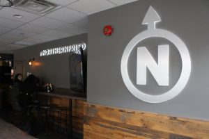 "Grey wall with logo of ""N"" surrounded by a white circle with an arrow pointing up."