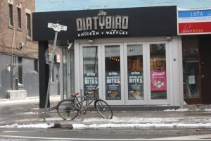"Exterior of Dirtybird Chicken and Waffles with bicycle and sign for ""Croft St."" in front."