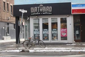 """Exterior of Dirtybird Chicken and Waffles with bicycle and sign for """"Croft St."""" in front."""