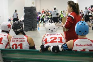 "Four women in jerseys reading ""Rocket, Commander Will Wrecker, Gigawats amd Babushkill"" sitting on bench next to coast."