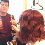 Back of woman's head and man looking at camera holding bottle and microphone.