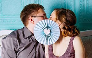 Man and woman kissing behind fan with heart in middle.