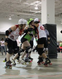 Women on roller skates on opposing teams colliding against each other