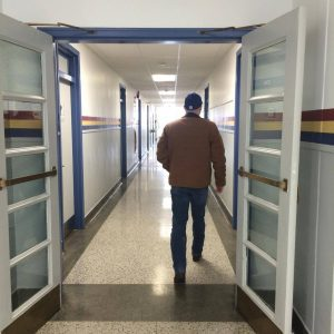 Man walking through white door down hallway with red, yellow and blue stripes.