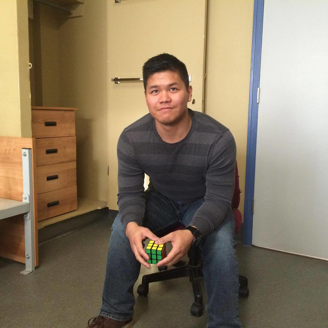 Man seated in office chair holding Rubik's cube
