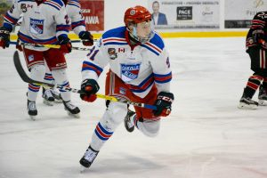 Hockey player skating with team in Oakville Blades jersey.