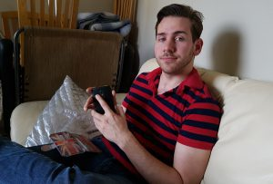 Josh sitting on white couch holding black phone and phone case with British flag on it.