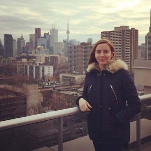 Woman in winter coat on balcony with Toronto skyline in background.