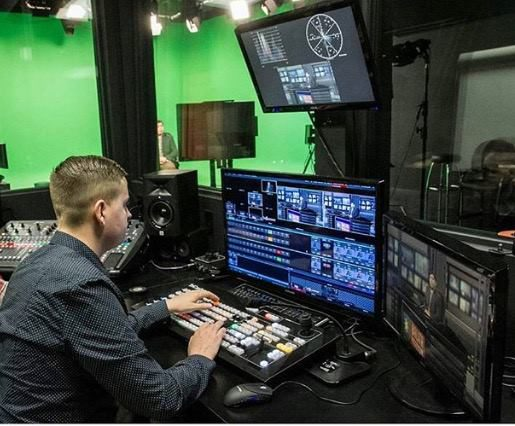 Man working in television studio with green screen in background.