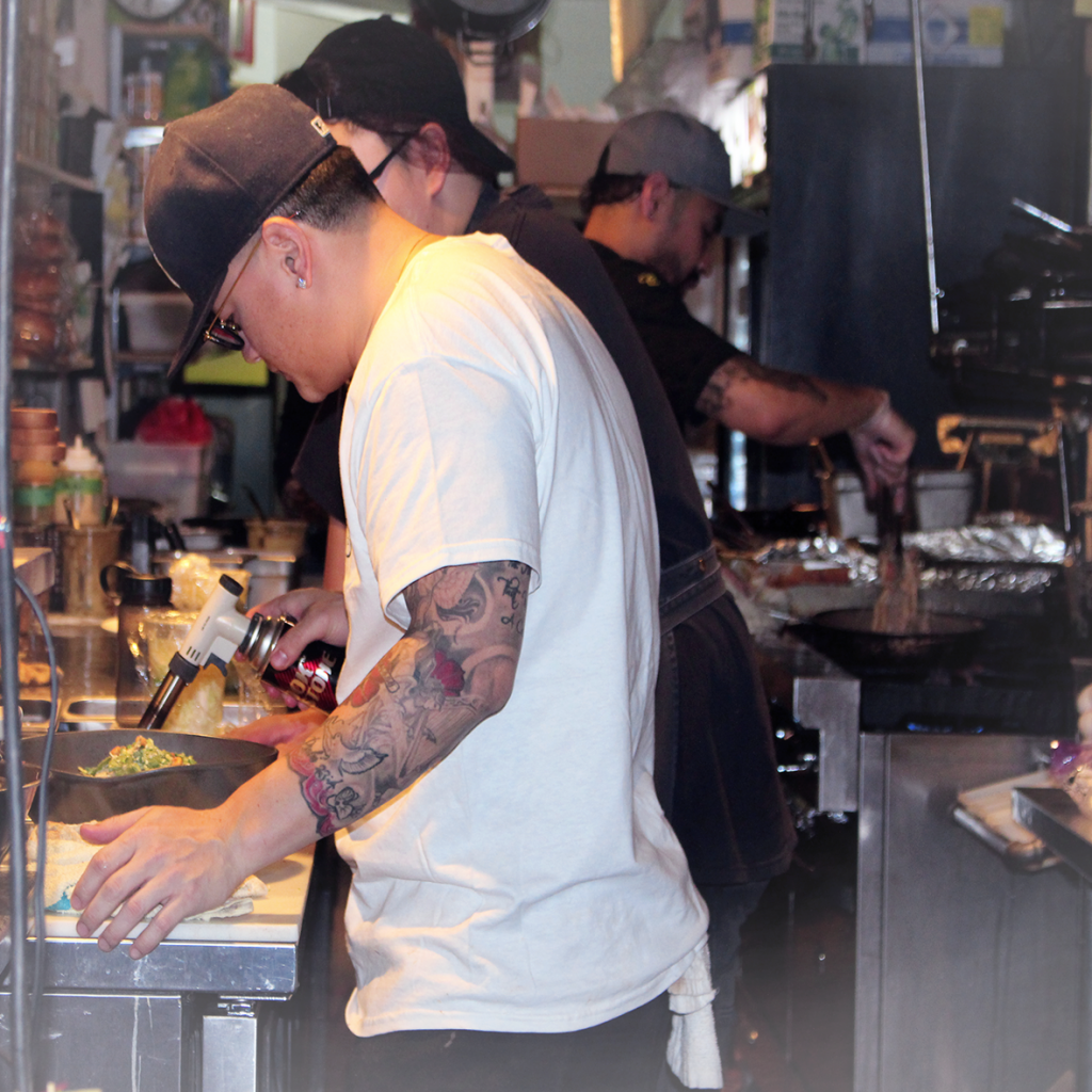 Man torching a dish in restaurant kitchen.