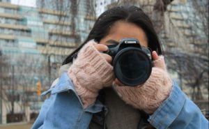 Woman wearing pink gloves taking photo with Canon camera.
