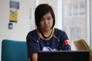 Judy Ngo wears sitting in jersey working on computer.