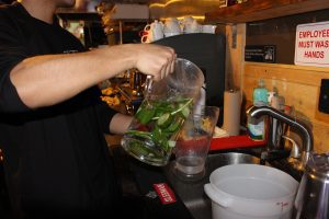 Man pours cucumber and mint water from jug into Sapporo glass.