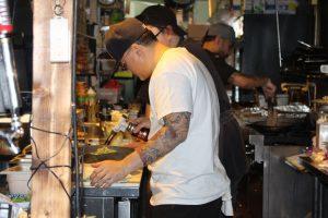 Man torching a dish in restaurant kitchen.