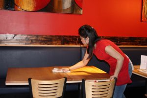 Woman using rag to clean empty table.