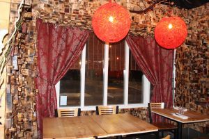 Seats surrounded by brown cube panelling and round red lights in Inspire Restaurant.