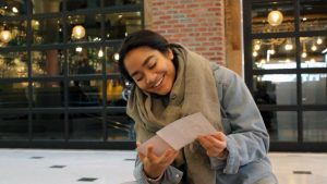 Woman sitting in front of brick building, looking at paper and laughing.