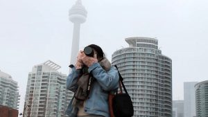 Woman taking photo with foggy CN Tower in background.