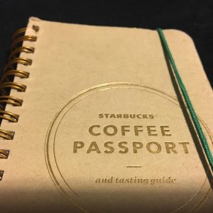"White notebook with ""Starbucks Coffee Passport and Tasting Guide"" written on front with green string."