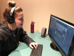 Woman wearing headphones edits audio at computer.