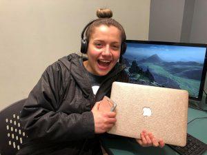 Woman wearing headphones in front of desktop computer holding laptop smiling.