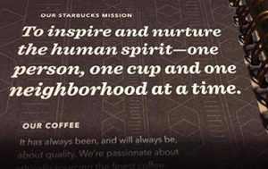 "Paper in book from Starbucks Coffee reading ""to inspire and nurture the human spirit- one person, one cup and one neighbourhood at a time""."