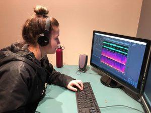 Woman wearing headphones edits audio at computer.