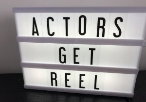 """Lightbox with black letters saying """"Actors Get Reel""""."""