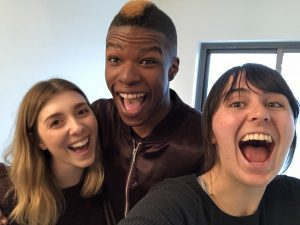 Two woman and a man smiling as they take a selfie.