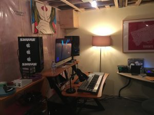 Recording studio with computer, keyboard and various pieces of art.