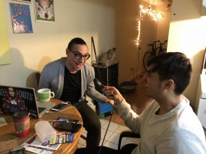Two men sitting together at table with laptop and microphone with cat in background.