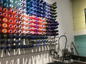 Wall with various rows of coloured sewing thread.