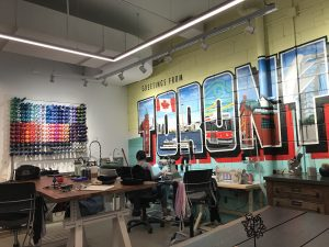 "Workspace with large wall of thread and mural that reads ""Toronto"" with images representing city inside."