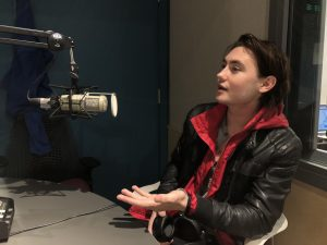 Actor Spencer Macpherson talking into microphone in radio studio.