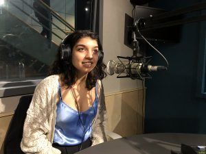 Woman wearing headphone talks into microphone in radio studio.