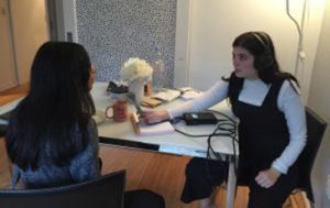 Woman wearing headphones interviewing woman across at table.