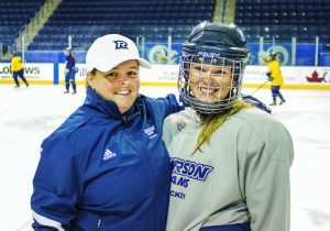 Woman in Rams hockey gear and woman in Rams jacket and hat smiling at camera on ice.