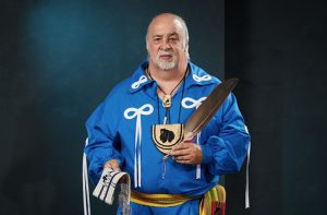 Elder Little Brown Bear wearing traditional clothing with yellow sash.