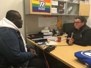 Man and woman sit across each other at desk with pride Rams flag on wall.