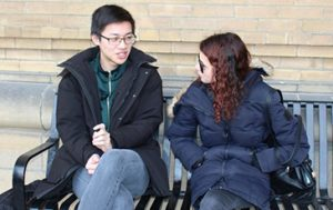Man and woman in winter coats sitting on bench talking.
