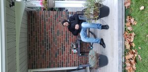 Man sitting in winter coat on patio in front of brick wall.