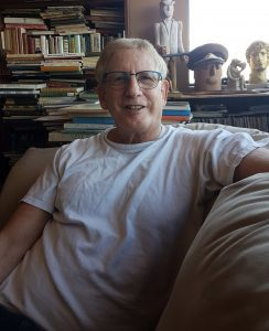 James Dubro sitting on couch in front of shelves of books and statues.