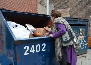 Woman sifting through blue dumpster.