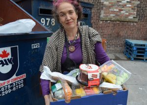Woman standing next to dumpster with box full of food.