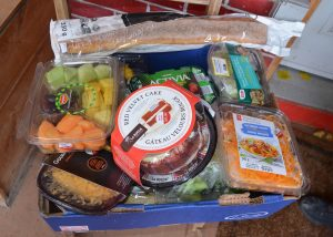 Box full of fruit, pasta, cake, bread and other foods.