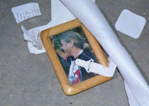 Framed photo of woman waving on floor next to discarded papers.
