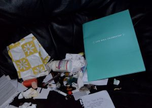 "Garbage including bottles, pens, wrappers and a book that says ""Life Well Celebrated""."