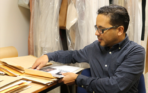 Man looking through papers in front of garment bags.