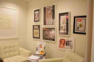 Cream coloured room with two framed magazines on wall.